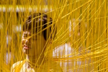 "Nico Navarro, 15, wades through a field of hanging ""spaghetti"" strings in Boston's Dewey Square as part of the Figment art festival, Sunday, July 28, 2013. PHOTO BY ERIN BALDASSARI/BOSTON METRO."