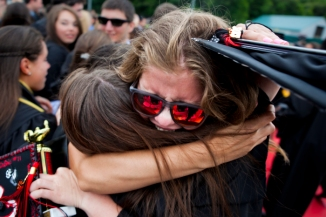 Watertown High School student Analise DeBaie hugged a fellow graduate after commencement at Victory Field June 1, 2012.