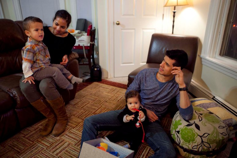 Harvard graduate student Adam Luck hangs out inside his Harvard-owned house on Western Avenue with his wife, Sarah, and two children, Orson, 2, and Amias, 8 months. Area residents Photo by Erin Baldassari/Wicked Local Cambridge.