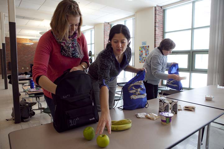 Weekend Backpack Program volunteers Stephanie Correia, left, Anne Carney, center, and Anne Ryan pack food into backpacks to send home to students at the Morse Elementary School in Cambridge, Friday, Feb. 14, 2014. Photo by Erin Baldassari/Wicked Local Cambridge.