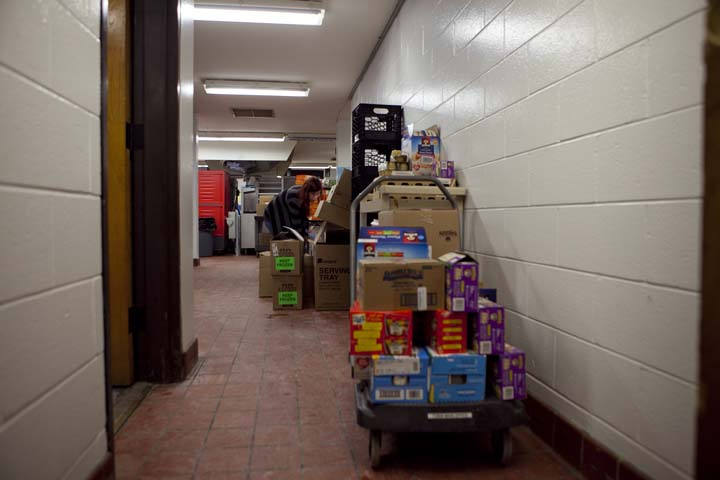 Alanna Mallon stacks boxes of food at the Tobin Elementary School in Cambridge that will be delivered to one of six elementary schools where volunteers will pack the food into individual backpacks for students whose primary source of nutritious food comes from the school district, Friday, Feb. 14, 2014. Photo by Erin Baldassari/Wicked Local Cambridge.
