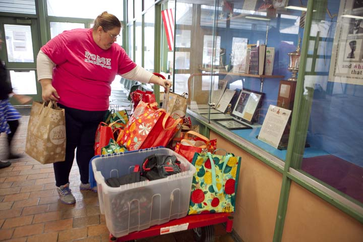 Morse Elementary School family liaison Denise Sullivan places backpacks packed with food in the front office for students to pick up on their way home, Friday, Feb. 14, 2014. For the week before spring vacation, students received two backpacks-worth of food. Photo by Erin Baldassari/Wicked Local Cambridge.
