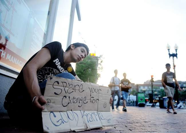 "Jose, 21, asks for spare change Tuesday morning, June 17, in Harvard Square. Known only as ""Taco"" on the street, Jose said he has been homeless for years. He has bounced in and out of several residential youth facilities since he was 14 years old. Wicked Local Staff Photo/David Gordon"