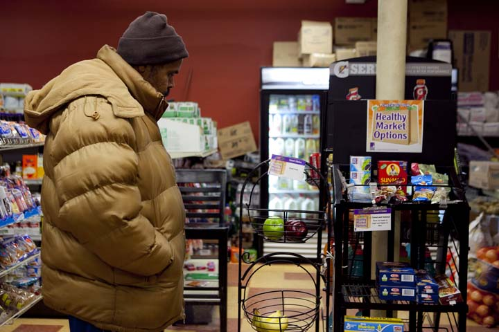 Cambridge resident Wayne Robinson eyes the Healthy Markets Program options at Newtowne Variety on Windsor Street, Thursday, March 6. The city selected two markets to launch the pilot program in December in an effort to make it easier for residents to eat healthy food. Photo by Erin Baldassari/Wicked Local Cambridge.