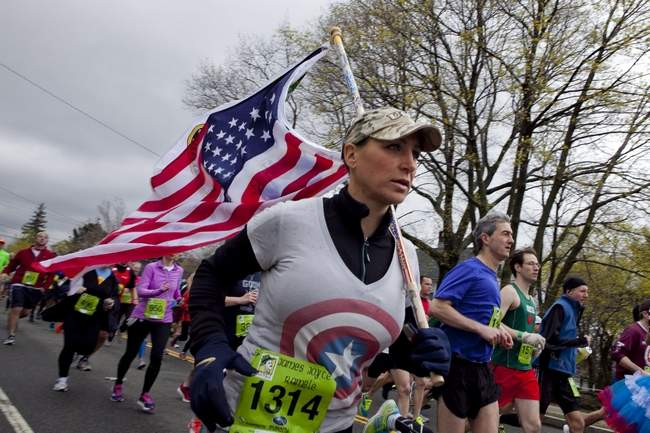 "Newton resident Heather Viveiros ran with an American and an ""All Gave Some, Some Gave All"" flag to support families of fallen veterans and veterans suffering from PTSD for the 20th annual James Joyce Ramble in Dedham, Sunday, April 27, 2014. Photo by Erin Baldassari/Wicked Local Dedham."