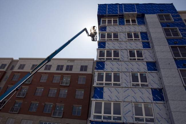 Construction workers continue work on a new apartment complex on Cambridge Park Drive, where hundreds of new residences have been constructed or permitted within the last few years. Wicked Local photo/Erin Baldassari