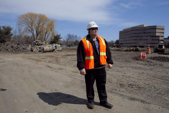 Callahan Inc. site superintendent Wayne Wendell stands in front of a lot on Cambridgepark Drive, which will soon hold over 200 apartments. Photo by Erin Baldassari/Wicked Local Cambridge.
