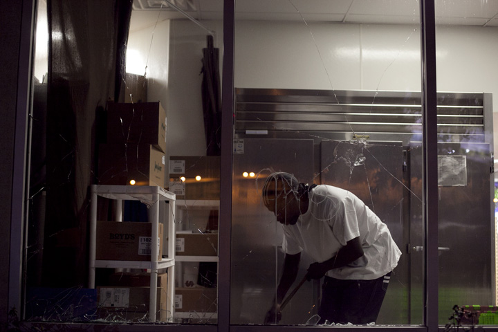 A store clerk at the Grand ARCO ampm cleaned up a broken window shattered by protesters during the third night of protests against a grand jury's decision not to indict Ferguson, Mo., Officer Darren Wilson in the Aug. 9 shooting death of Michael Brown, Wednesday, Nov. 26, 2014. Photo by Erin Baldassari/Bay City News Service.