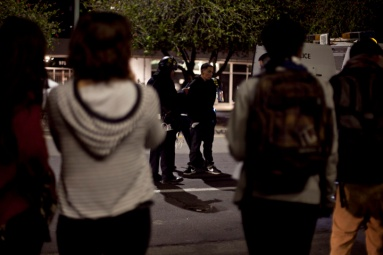Protesters gathered to film and watch police while they arrest a fellow protester during the third night of protests in Oakland against a grand jury's decision not to indict Ferguson, Mo., Officer Darren Wilson in the Aug. 9 shooting death of Michael Brown, Wednesday, Nov. 26, 2014. Photo by Erin Baldassari/Bay City News Service.