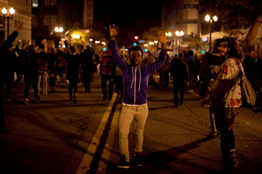 Police herded protesters at a brisk pace in downtown Oakland during the third night of protests against a grand jury's decision not to indict Ferguson, Mo., Officer Darren Wilson in the Aug. 9 shooting death of Michael Brown, Wednesday, Nov. 26, 2014. Photo by Erin Baldassari/Bay City News Service.