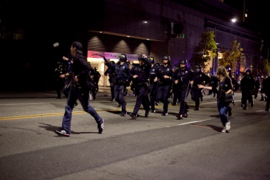 Police rushed protesters along downtown Oakland streets during the third night of protests against a grand jury's decision not to indict Ferguson, Mo., Officer Darren Wilson in the Aug. 9 shooting death of Michael Brown, Wednesday, Nov. 26, 2014. Photo by Erin Baldassari/Bay City News Service.
