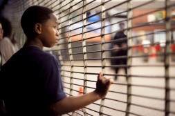 A young boy grabbed at the metal gate prohibiting protesters from enterting the West Oakland BART station during the third night of protests in Oakland against a New York grand jury's decision not to indict a white police officer in the chokehold death of Eric Garner, Friday, Dec. 5, 2014.