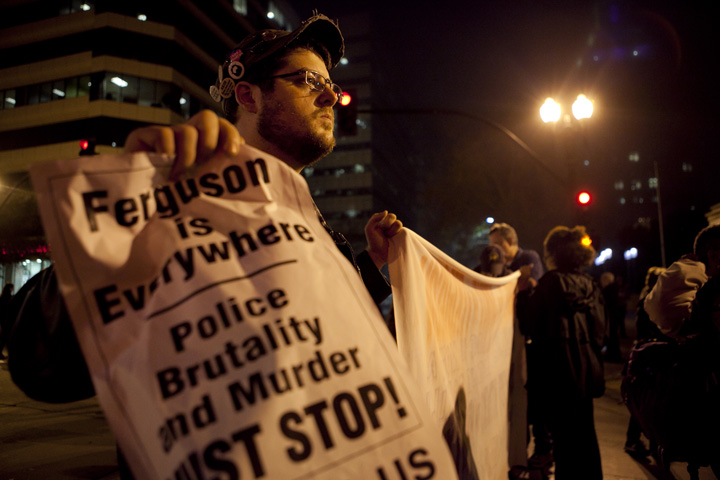 Will Landrum of Livermore held a banner decrying police brutality before marching with demonstrators in Oakland to protest a grand jury's decision not to indict a New York police officer in the choke-hold death of Eric Garner, Thursday, Dec. 4, 2014. Photo by Erin Baldassari/Bay City News Service.