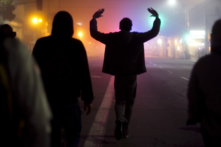Demonstrator Aaron Weathers held up his arms while marching down International Avenue in Oakland for the second day of protests against a grand jury's decision not to indict a New York police officer in the choke-hold death of Eric Garner, Thursday, Dec. 4, 2014. Photo by Erin Baldassari/Bay City News Service.