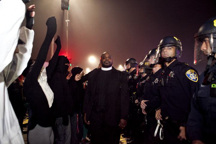 Associate Pastor Ben McBride walked between protesters and police during a demonstration in Oakland against a grand jury's decision not to indict a New York police officer in the choke-hold death of Eric Garner, Thursday, Dec. 4, 2014. McBridge said he was there to keep the peace. Photo by Erin Baldassari/Bay City News Service.