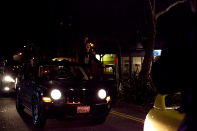 A woman in her car stood up in solidarity with demonstrators, who took to the streets in Berkeley and Oakland for the sixth night in as many days to protest two grand jury decisions not to indict white police officers in the deaths of unarmed black men, Wednesday, Dec. 10, 2014. Photo by Erin Baldassari/Bay City News Service.