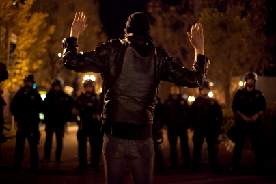 A demonstrator confronted a line of police officers in Oakland during the sixth night of protests against two grand jury decisions not to indict white police officers in the deaths of unarmed black men, Wednesday, Dec. 10, 2014. Photo by Erin Baldassari/Bay City News Service.