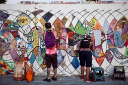 Attendees paint on an art wall at the Bay Area Vibez Festival at the Middle Harbor Shoreline Park, Sunday, Sept. 28, 2015. Photo by Erin Baldassari/East Bay Express.
